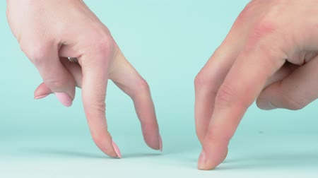 confronto : male and female hand on blue background walking fingers each other