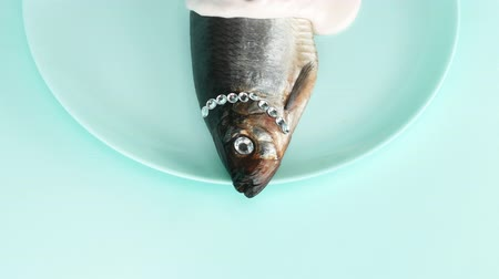 surrealismo : fashion design food. fish herring with rhinestone, pink sauce and a confetti
