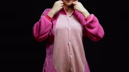 espectador : girl in pink pajamas kigurumi in VR glasses on a black background. pajama party