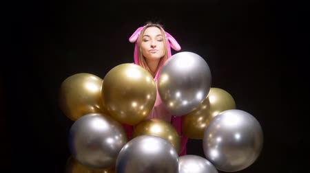 celebration event : girl in pink kigurumi pajamas with balloons. pajama party