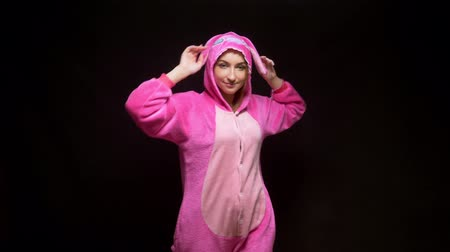 peluche : girl in pink pajamas kigurumi in VR glasses on a black background. pajama party