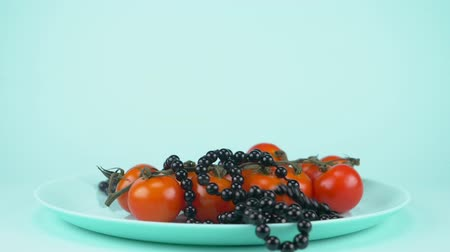 peas : food design a branch of cherry tomatoes on a plate. black beads fall from above Stock Footage