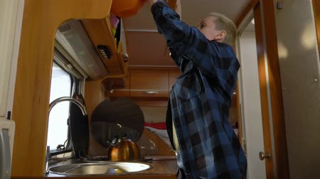 csavargó : A woman washes dishes in a motorhome. car travel concept