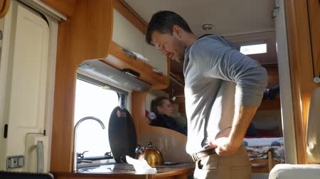 csavargó : A man washes dishes in a motorhome. car travel concept Stock mozgókép