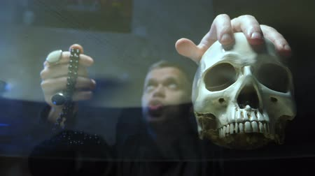 büyücü : view through a glass countertop. the magician casts a spell. hand on its skull Stok Video