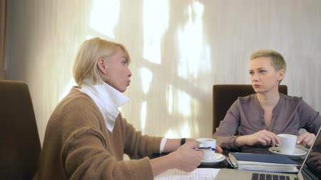 pracodawca : two women are talking while sitting in an office in front of a laptop