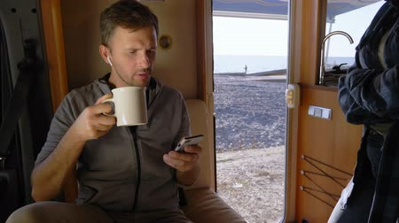 hippie : man drinks coffee and uses a smartphone sitting in a caravan by the sea