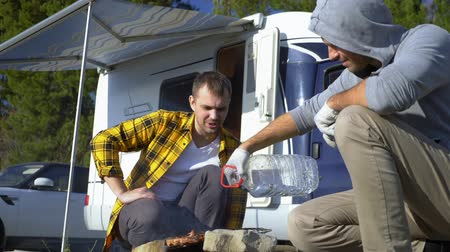 hippie : Two men cook meat on the grill near the campervans in nature Stock Footage