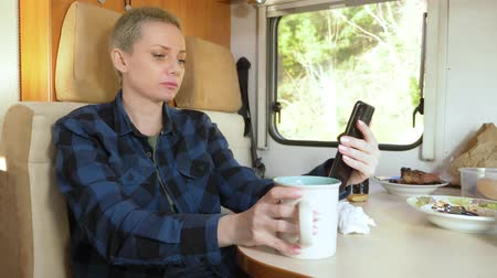 hippie : woman uses a cell phone while sitting at a table in a motorhome