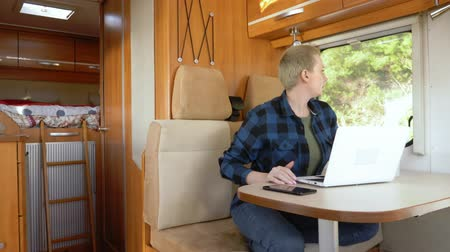 hippie : A woman uses a laptop while sitting at a table in a motor home.
