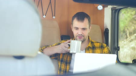 ヒッピー : man using his laptop sitting at a table in the motorhome