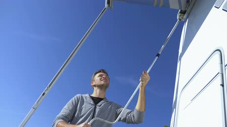 навес : A man sets up a canopy from the sun on a motor home against a clear blue sky