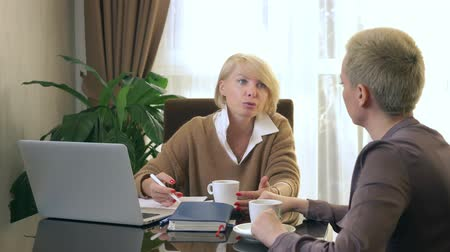 formální : two women are talking while sitting in an office in front of a laptop