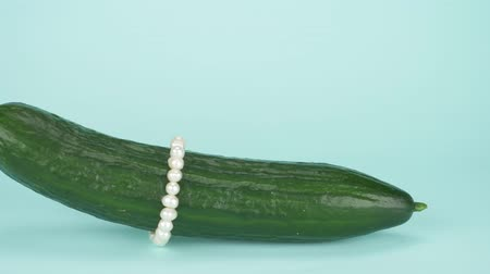 экзотичность : fashion art food design. Fresh cucumber with a string of pearls. blue background Стоковые видеозаписи