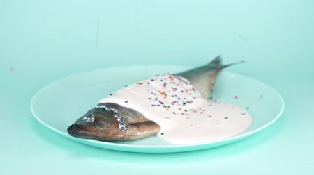 mayonaise : fashion food. fish herring with rhinestone, pink sauce and a colorful confetti