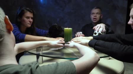 feiticeiro : A session of spiritualism group of people sitting at a round table holding hands