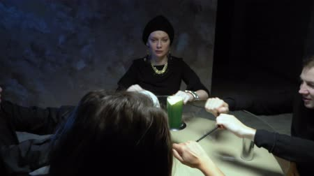 kultusz : A session of spiritualism group of people sitting at a round table holding hands