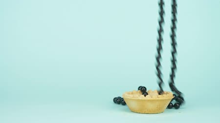 boncuklar : fashion art. minimalism. the black beads fall into the tartlet. blue background Stok Video