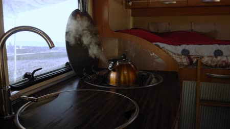 hippie : the kettle boils on the stove in the motorhome. the steam from the kettle.
