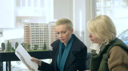estate agency : two women are talking, sitting in the sales office on the background of the layout of the building Stock Footage