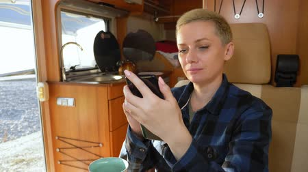 ヒッピー : woman uses a cell phone while sitting at a table in a motorhome