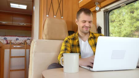 hippie : man using his laptop sitting at a table in the motorhome