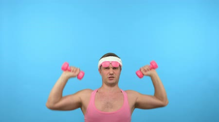 szörnyszülött : Playful handsome man in a pink shirt is engaged in fitness with pink dumbbells. Bright Fitness. Sports fashion accessories