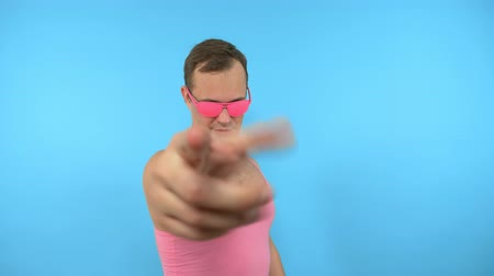 урод : crazy man in pink glasses come here gesture on blue background