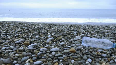 discarded : plastic trash on the stone seashore. environmental problems