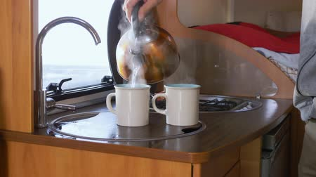 hippie : a man pours boiling water into mugs in a motorhome. steam from the kettle.