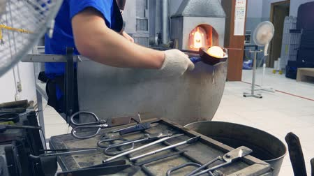 olvasztott : glassblower. manufacturer of glass products. man heats glass in a furnace Stock mozgókép