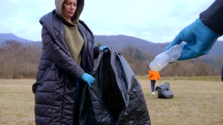 activist : environmental problems. a group of volunteers removes trash in the forest Stock Footage
