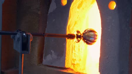 fundido : glassblower. manufacturer of glass products. man heats glass in a furnace Stock Footage