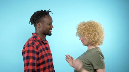 blue braid : African man and Caucasian woman with Afro hairstyle. blue background