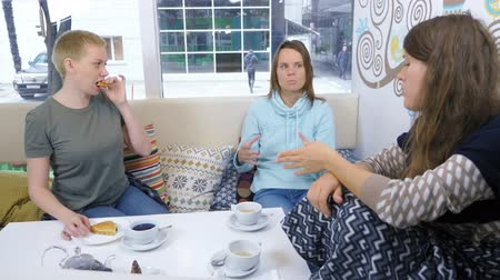informal : three women relax together in an informal cafe. friendly gatherings