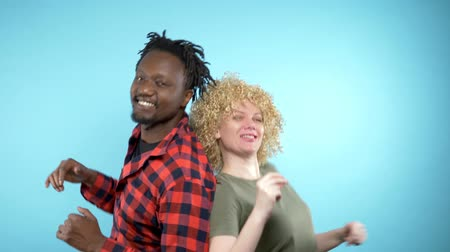 blue braid : African man and Caucasian woman with Afro haircut is dancing. blue background Stock Footage