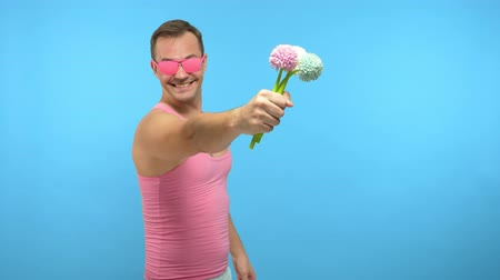 урод : handsome man freak in pink glasses with a bouquet of flowers. blue background