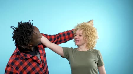 braid hairs : African man and Caucasian woman with Afro hairstyle. blue background