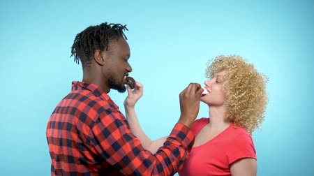 abraços : African man Caucasian woman eating black and white marshmallows. blue background