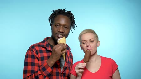 şeker : African man, Caucasian woman eating chocolate and cream ice cream. Stok Video