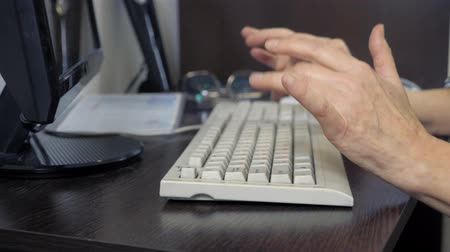 e mail address : closeup hands of an elderly woman typing on a keyboard