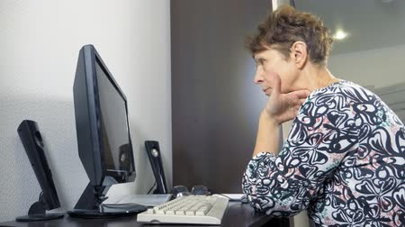 madurez : elderly woman at the computer sits at a table in the home office
