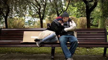 bezrobotny : a homeless couple, a man and woman on a bench in a city park