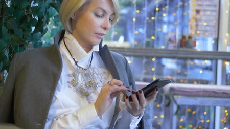 aplikace : elegant stylish blond woman using mobile phone sitting in a cafe