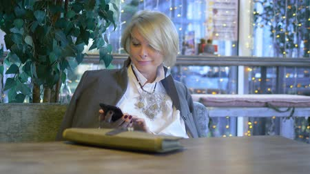 kahve molası : elegant stylish blond woman using mobile phone sitting in a cafe