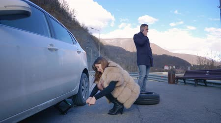 урод : humor. woman changing a car wheel. man talking on the phone Стоковые видеозаписи