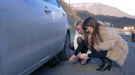 lekke band : two girls change a flat tire on the car on the side of the road. Stockvideo