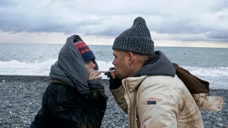 barbone : homeless couple, man and woman smoking on the seashore Filmati Stock
