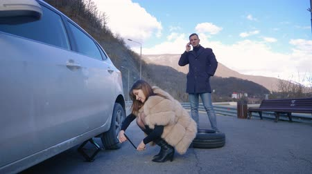 replace : humor. woman changing a car wheel. man talking on the phone Stock Footage