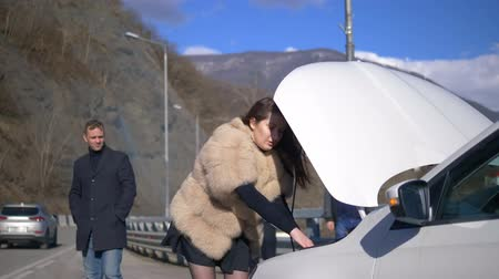 beira da estrada : the girl looks under the bumper of the car, men remove it on the phone Stock Footage